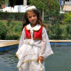 A young child is wearing a traditional white cloth with a red waistcoat.