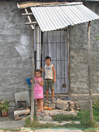 Two chilren stand in front of a poor house.