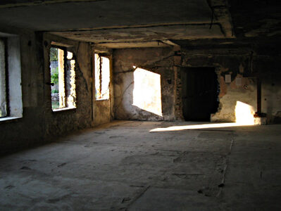 An empty room, with no furniture, and with its walls partly demolished.