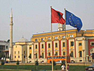 Albanian and European Union's flag wave next to each other in front of a large calssical building