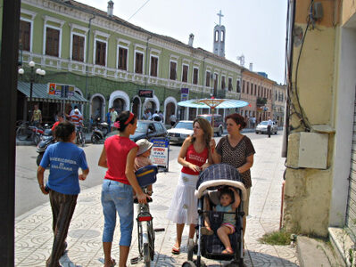 In a street with coloured renovated buildings, ladies with children talk quietly.